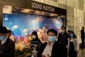 Pedestrians wearing protective masks walk past a Louis Vuitton shop in Central, Hong Kong. Several luxury brands have seen a drop in sales in China thanks to the spread of the coronavirus. Photo: Bloomberg