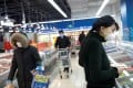 People in protective face masks in a Beijing supermarket on February 19, 2020. The public health crisis could be a long-term growth catalyst for supermarket chains that have integrated online and offline channels. Photo: Reuters