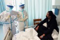 Respiratory and critical care specialists check up on a patient at Wuhan's Tongji Hospital. Photo: Xinhua
