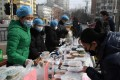 Restaurant workers in protective face masks as they sell packaged meals in a car park outside their restaurant in Beijing on February 21, 2020. Photo: AFP