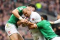 Ireland's Bundee Aki (right) tackles England's Jamie George (centre) during their Six Nations match at Twickenham. Photo: EPA