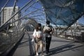 People wearing face masks walk along the Helix Bridge in Singapore earlier this month. Photo: EPA
