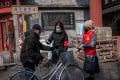 Community volunteers wearing protective face masks and gloves take the temperature of a man on a street in Beijing. Photo: AFP