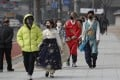 Visitors wearing face masks walk near the Gwanghwamun, the main gate of the 14th-century Gyeongbok Palace, in Seoul, South Korea, on February 22. South Korea become the country worst-hit by the coronavirus after China, after two rapid clusters of infections emerged, linked to a church and a hospital. Photo: AP