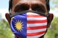 A supporter of the People's Justice Party wears a Malaysian flag face mask outside the National Palace in Kuala Lumpur. The recent high-profile resignations have caused political instability in the country as it handles the coronavirus outbreak. Photo: Reuters