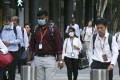 Commuters wearing protective masks at the Marina Bay business district in Singapore on Wednesday, Feb. 12, 2020. Photo: Bloomberg