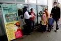 A commuter line medical officer provides masks to passengers at the Depok Baru Train Station in Depok, West Java, Indonesia. Photo: EPA-EFE