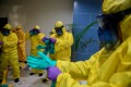 Indonesian officials put on protective suits before coming in to contact with possible coronavirus patients on Sunday. Photo: Reuters