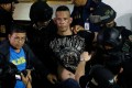 Archie Paray, the gunman who took dozens hostage inside a mall, is arrested by police in San Juan, Metro Manila. Photo: Reuters