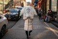 A person wears a protective mask while walking with an umbrella in New York's Chinatown neighbourhood. Photo: Bloomberg