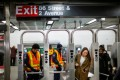 MTA workers disinfect turnstiles at a subway station in Manhattan on Wednesday. Photo: Reuters