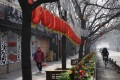 A woman walks past Lunar New Year decor and shuttered bars at a retail district in Beijing in February 2020 as millions of workers and entrepreneurs bear the rising costs of coronavirus containment measures. Photo: AP