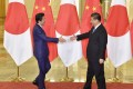 Chinese President Xi Jinping (right) and Japanese Prime Minister Shinzo Abe shake hands ahead of their talks at the Great Hall of the People in Beijing in 2019. Photo: Kyodo