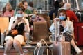 Travellers wearing protective masks at Changi International Airport in Singapore. Photo: AFP