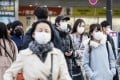 Commuters seen in protective masks in Tokyo on February 25, 2020. Photo: Bloomberg