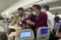 Video taken on board a Thai Airways flight at Shanghai on Friday purports to show flight attendants trying to control a passenger who coughed on one of their colleagues. Photo: Handout