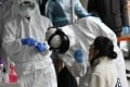 Medical staff wearing protective gear take samples from people at a temporary virus test facility in Seoul. Photo: AFP