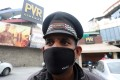 An Indian security guard wears face mask as he stands outside the closed PVR cinema hall in Jammu, India on Wednesday. Photo: EPA-EFE