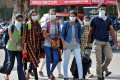 A group of students in protective masks walk outside a railway station in Kochi on March 10, 2020. Photo: Reuters