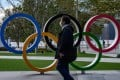 A man wearing a face mask walks in front of the Olympic Rings in Tokyo. There are increasing calls to delay the Summer Games. Photo: AFP