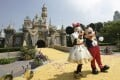 Employees in Mickey and Minnie Mouse costumes wave in front of the Sleeping Beauty Castle at Disneyland in Anaheim, California, in July 2005. Photo: AFP