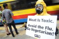 An activist from People for the Ethical Treatment of Animals (PETA) wears a hazmat suit to warn of the health risks of eating meat, at a protest in November 2010 in Hong Kong. Photo: Handout