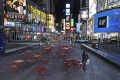 A woman walks through a lightly trafficked Times Square in New York, Monday, March 16, 2020. Bars and restaurants will become takeaway-only and businesses from cinemas and casinos to gyms and beyond will be closed. Photo: AP