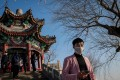 A man wearing a face mask as a preventive measure against the Covid-19 disease walks at the Summer Palace in Beijing, on Tuesday. China's domestic travel is set to rise after authorities relax curbs imposed in the wake of the coronavirus outbreak. Photo: AFP