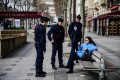French police officers talk to a woman sitting on a bench of the Champs-Elysees avenue in Paris on March 17, as a strict lockdown came into in effect to stop the spread of the Covid-19 in the country. Photo: AFP