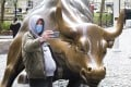 A man in a protective mask takes a selfie with the Charging Bull statue in New York. US markets rallied on Thursday after the Federal Reserve took steps to boost liquidity. Photo: EPA-EFE