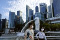 A couple wearing face masks walks past the Merlion statue in Singapore. Photo: AP