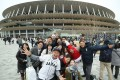People pose in front of the main Olympic Stadium in Tokyo, with the Japanese government determined the Games will go ahead as planned. Photo: AFP