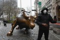 A man wearing a face mask takes a picture at the charging bull statue near the New Stock Exchange on Monday. Stocks on Wall Street fell early as Congress wrangled over a massive stimulus package. Photo: AFP