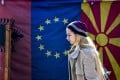 A woman walks in front of flags of Albania, the EU and North Macedonia in a bazaar in Skopje. Photo: EPA-EFE