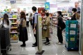 Japanese people queue at a pharmacy in Tokyo. Photo: Reuters