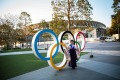 A woman wearing a traditional Japanese kimono poses next to the Olympic rings in front of the Japan National Stadium. Photo: AFP
