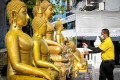 A volunteer disinfects Buddha statues before a televised anti-plague prayer at Wat Traimit Temple, Bangkok, amid lockdown restrictions to contain the spread of the coronavirus. Photo: AFP