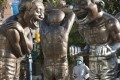 A woman wears a face mask as she walks past statues at English Bay in Vancouver, British Columbia, on Tuesday. Photo: AP