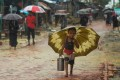 A young Rohingya refugee shelters under an umbrella as he makes his way amid monsoon rains at Kutupalong refugee camp in Bangladesh on September 12, 2019. Photo: AFP