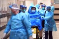 Medical staff transfer a patient suspected as a Covid-19 case at Queen Elizabeth Hospital in Hong Kong. Photo: Reuters