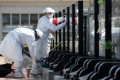 Staff wearing protective suits and face masks sweep tombs on behalf of families at the Babaoshan Cemetery in Beijing. Photo: Reuters