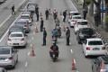 Police officers check vehicles to enforce the coronavirus lockdown in downtown Kuala Lumpur, Malaysia. Photo: AP