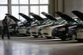 A man walks past cars at an assembly line producing electronic cars at a factory of Beijing Electric Vehicle, funded by BAIC Group, in Beijing, China. Photo: Reuters
