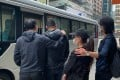 Suspected members of the gambling syndicate being led into a police van. Photo: Handout