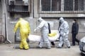 Funeral home workers remove the body of a person suspect to have died from a virus outbreak from a residential building in Wuhan in early February. Photo: AP