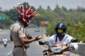 Police inspector Rajesh Babu, wearing a helmet depicting the coronavirus, asks a motorcycle rider to go home in Chennai, India, on Saturday. Photo: Reuters