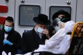 Hasidic men speak with an elderly patient being brought into Mount Sinai Hospital amid the coronavirus pandemic on April 1, 2020 in New York City. Photo: Agence France-Presse