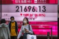 Pedestrians wearing face mask walk past a bank electronic board billboard displaying the Hang Seng Index in Central on March 23, 2020. Photo: Edmond So