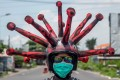 An Indonesian police officer wearing a coronavirus-themed helmet conducts a hygiene awareness campaign in Mojokerto, East Java on April 3. Photo: AFP
