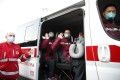 Doctors and paramedics from China wave on a Red Cross vehicle after arriving at Malpensa airport, Milan, on March 18, part of a team of 37 and a shipment of 20,000 tonnes of equipment sent to help Italy. Photo: AP